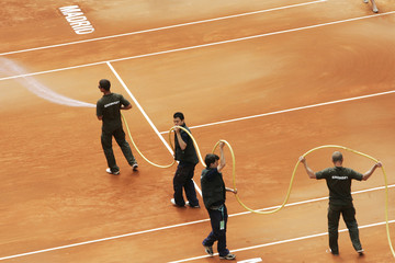 Workers hose down the court during the Madrid Open tennis tournament match between Serena Williams and Francesca Schiavone in Madrid