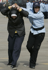 A policewoman demonstrates her arrest skills during a graduation ceremony at a police academy in Baghdad