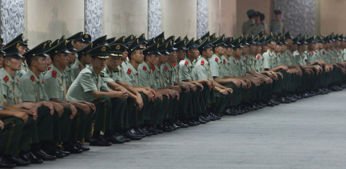 Paramilitary policemen wait in the tunnel under Tiananmen square after the Beijing 2008 Olympics torch relay