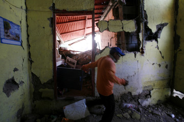 Earthquake victim Jorge Araya removes debris from his destroyed home in Tocopilla
