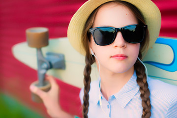 Young hipster girl with braids in sunglasses and straw hat with a longboard on her shoulders - against a red vivid wall