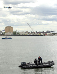 Members of NYPD Aviation, Marine and Dive teams work the East River site of a downed helicopter in New York.