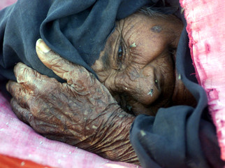An sick and elderly Indian woman lies on the ground at a makeshift camp for earthquake survivors in ..
