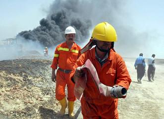 TWO IRAQI FIREMEN BATTLE BURNING OIL PIPELINE NEAR BASRA.