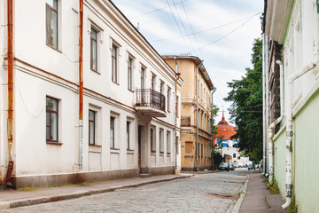 Old houses in Vyborg, Russia. Buildings with old fashioned windows and downpipes. Round Tower in the end of street.