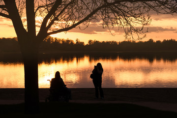 A photographer is taking a photo for a person in wheelchair under sunset