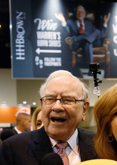 Berkshire Hathaway chairman and CEO Warren Buffett smiles in front of a photo of himself before the Berkshire's annual meeting in Omaha