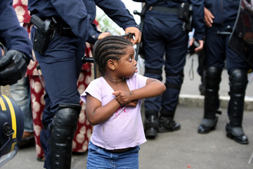 Child looks at riot policemen after police evacuated about 1, 000 people from France's biggest squat near Paris