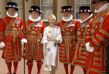 Australian singer Minogue poses with Yeoman Warders after receiving an OBE at Buckingham Palace in London