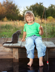 Happy boy go fishing on the river with pet, one children and kitten of the fisherman with a fishing rod on the shore of the lake.