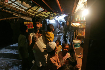 Homeless people wait to buy goods from a makeshift shop beside pipelines in Bombay.