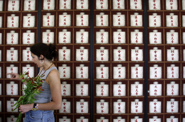 A worker carries flowers in front of painting of Chinese traditional medicine bottles during preparation of the new Lisbon's Orient Museum