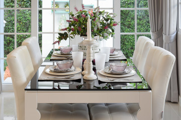 dining table and comfortable chairs in vintage style with elegant table setting