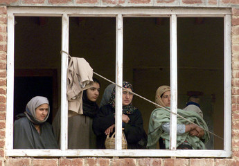 A GROUP OF KASHMIRI WOMEN WATCH FROM A WINDOW POLICE REMOVING IED'S INSRINAGAR.