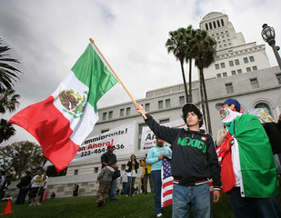 Bracamontes waves a flag while standing with Sandoval outside the Los Angeles City Hall