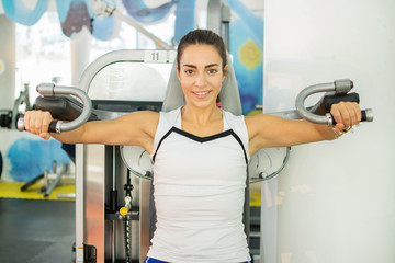 Young smiling woman doing exercises on gym machine.