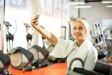 Young blonde girl making selfie photo on smartphone during workout break in gym.