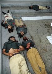 BODIES OF FIVE PAKISTANI POLICEMEN LIE IN A HOSPITAL IN KARACHI.