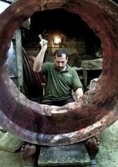 AN IRAQ MAN MAKES METAL BARREL IN HIS WORKSHOP IN BAGHDAD.