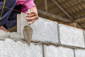 Close up bricklayer worker installing brick masonry on construction site