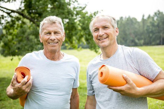 Two men with yoga mats, smiling