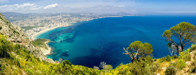 Panoramic landscape of Calpe. Ascension and hiking in the Rock of Ifach. Vacation and sunshine tourism on the beaches of Alicante, Spain.