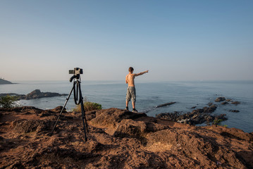 video blogger outside. shoots video with a tripod over sea.