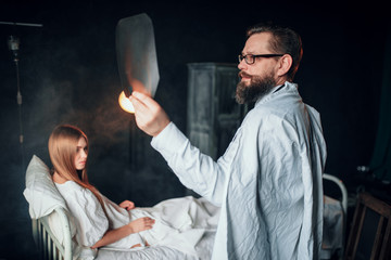 Male doctor looking at x-ray picture of sick woman