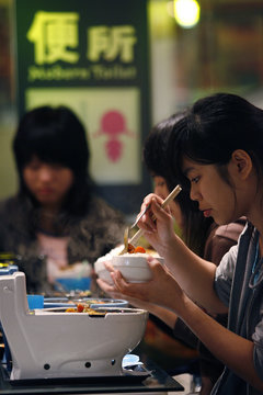 A customer eats a set meal shaped like a toilet bowl at the Modern Toilet diner in Taipei