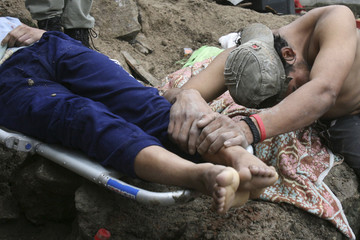 A man cries over the body of his relative after a wall fell on a house in Tegucigalpa