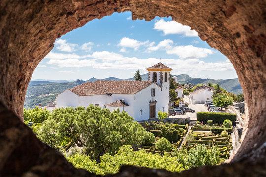 Church of portuguese town of Marvão seen through a hole