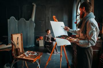 Painter drawing portrait against female poseur