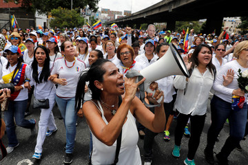 A demonstrator shouts slogans during a women's march to protest against President Nicolas Maduro's government in Caracas,