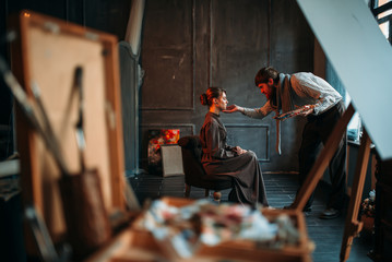 Male artist work with female poseur in art studio