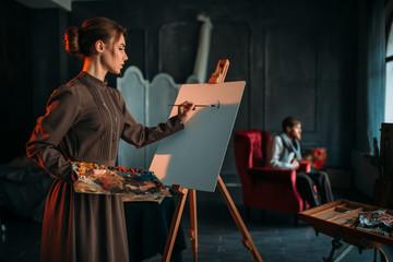 Female painter paints man portrait in art studio