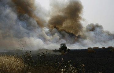 An Israeli firefighter tries to extinguish a fire in a wheat field after a rocket attack near Sderot