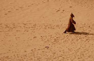 A man walks at a Ighzer Ksar on the outskirts of the oasis town of Timimoun