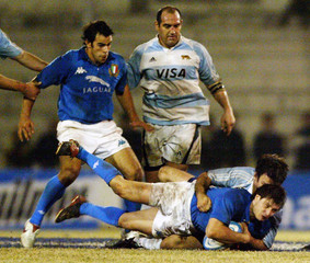 Italy's Pez is tackled by Argentina's Schusterman as team mates look on during a rugby test match ...