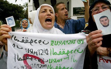 An Algerian mother holds up a photograph of her disappeared son during a protest outside the office of a human rights group in Algiers