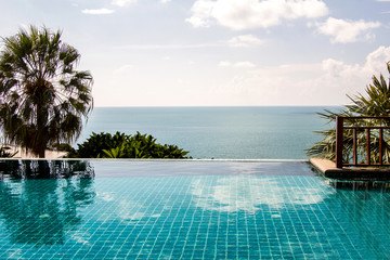 Swimming pool looking at blue sea view and blue sky background