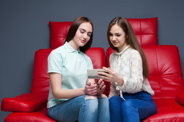 Two young women looking at pictures on phone