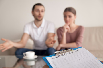Unhappy man telling family psychologist his opinion about problems in marriage while his unsatisfied wife sitting next to husband during therapy session. Couple consulting relationships expert