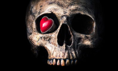 old heart shape ring in eye socket of human skull on black background