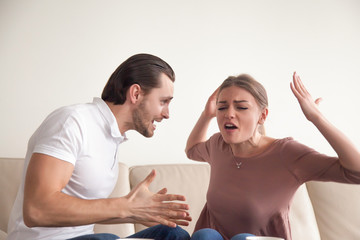 Portrait of angry couple fighting, screaming, shouting and blaming each other for problems, quarrels, negative emotions, difficulties in relationships, misunderstanding in marriage, it is your fault