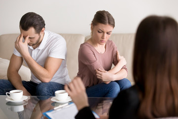 Trusted family relationships expert working with young couple after quarrel not talking to each other, helping to understand and find compromise, repeated fights, conflicts, marriage therapy guidance