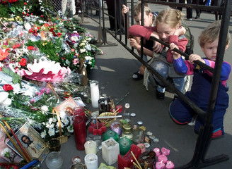 Russian children look at candles, icons and flowers outside the American embassy in Moscow, Septembe..