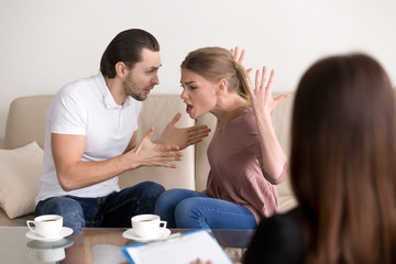 Angry aggressive couple quarrelling, screaming, shouting and blaming each other for problems while consulting family relationships expert or marriage counselor, negative emotions and hysterics