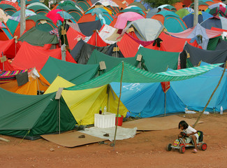 "Thai girl displaced by tsunami rides her newly acquired wheels at ""tent city"" in Takuapa, Thailand."