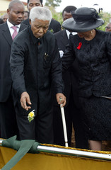 Former South African President Nelson Mandela throws a corsage into the grave of his oldest ...