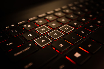 Black Laptop Computer Keyboard With Different WASD Buttons, and Illuminated Red Backlight